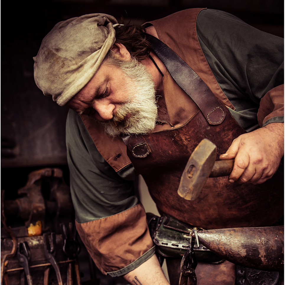 Work the Faire Blacksmith Marketplace Vendor Merchant Man hammer. photo by D. Grosmark