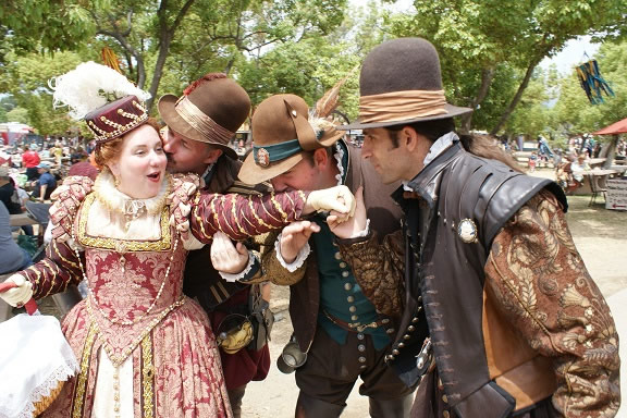 Noble lady of the court being wooed by several gentlemen using Elizabethan language at the Renaissance Pleasure Faire.
