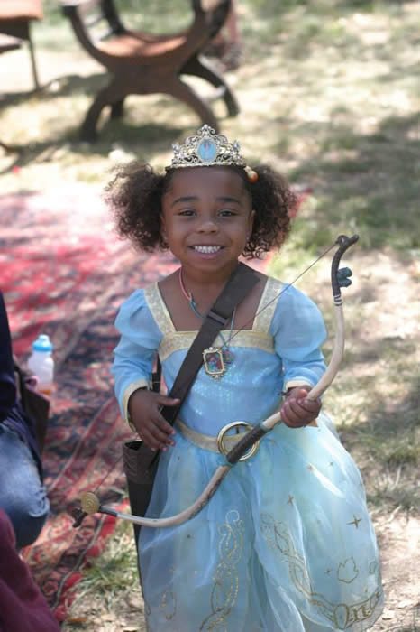 smiling child in princess dress holding bow and arrow for the photos, videos and press page